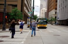 People running across a street to catch a bus.