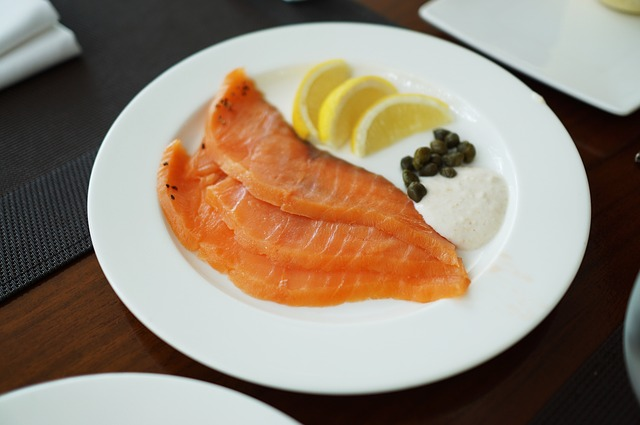 a plate of smoked salmon with sour cream, lemon and capers.
