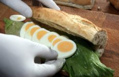 An egg sandwich being assembled on a baguette with lettuce.