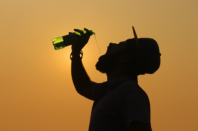 A person drinks from a water bottle in high temperatures.