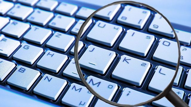 A computer keyboard being inspected with a magnifying glass.