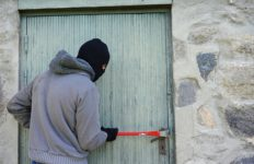 A thief prys open a door with a crowbar.