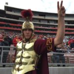 A USC Trojan mascot in roman battle gear costume with helmet and plume raises his arm to give a V for victory gesture.