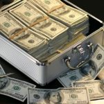 A luggage case filled with bundles of $100 bills. Photo from Pixabay.