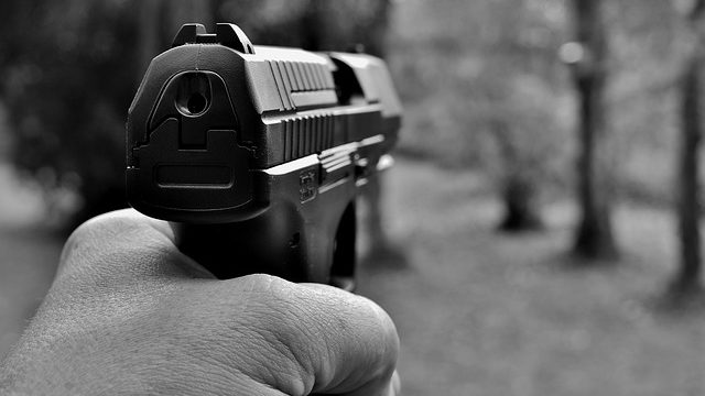 An automatic handgun being aimed at a target. Photo from Pixabay.