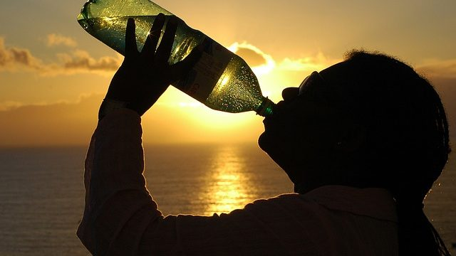 A person drinks from a bottle during a heatwave. Photo from Pixabay.