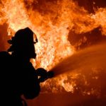 A firefighter uses a fire hose on a raging blaze. Photo from Pixabay.