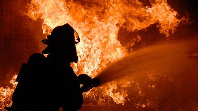 A firefighter uses a fire hose on a raging blaze. Photo from Pixabay.