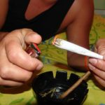 A person lighting a big marijuana cigarette, or joint. Photo from Pixabay.