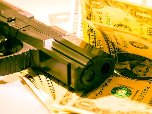 A gun and money. Photo from Pixabay.