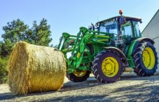 An example of a tractor lifting a bale of hay in the field. Photo from Pixabay.