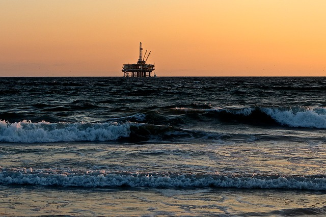 An oil rig sits in the ocean near a beach. The Trump administraton has announced the opening of all offshore waters to oil drilling. Photo from Pixabay.