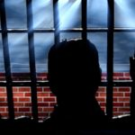 An illustration of a man in a prison cell. Image from Pixabay.