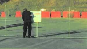 "Unidentified man removes a City of Walnut ""stop-work"" sign from stadium perimeter fence on Feb. 22."