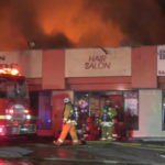 Firefighters outside burning strip mall