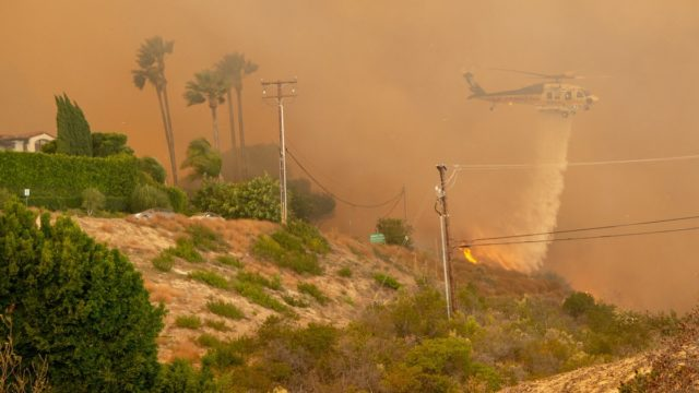 Helicopter drops water on flames from the Woolsey Fire