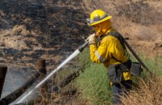Firefighters sprays water on hot spot