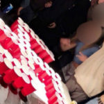 Students appear to salute a swastika made of red drinking cups