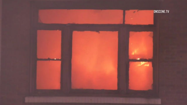 Flames are visible through a window in the building