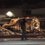 Police officer walks by wreckage