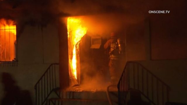 Firefighters at door to burning residence