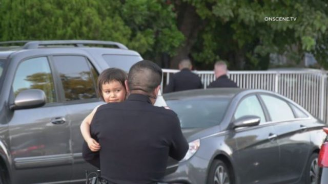 Police officer carries orphaned child