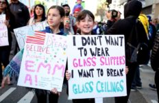 Young women hold signs