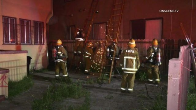Firefighters outside burning apartment