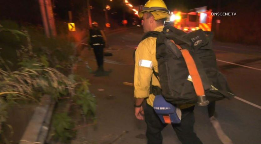 Firefighters rush to battle the blaze in the Sepulveda Pass