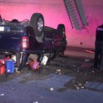 Police with suspect outside wrecked vehicle